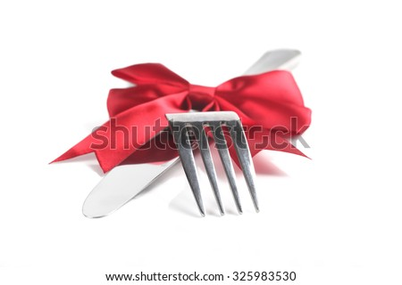 Fork and knife with christmas ribbon, isolated on white, shallow focus - stock photo