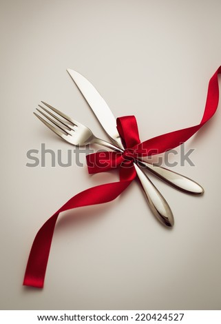 Fork and knife with decorative ribbon.