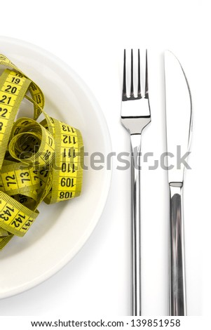 Fork and knife with metric tape in dish - stock photo