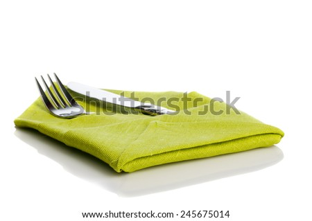 Fork and knife wrapped in green cloth for table setting isolated on white background - stock photo
