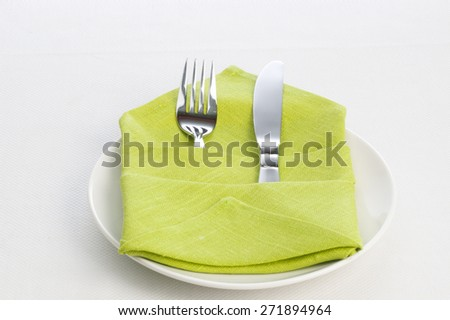 Fork and knife wrapped in green cloth on plate for table setting on gray background - stock photo
