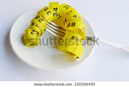 Fork and measuring tape on a plate as a symbol of healthy dieting - stock photo
