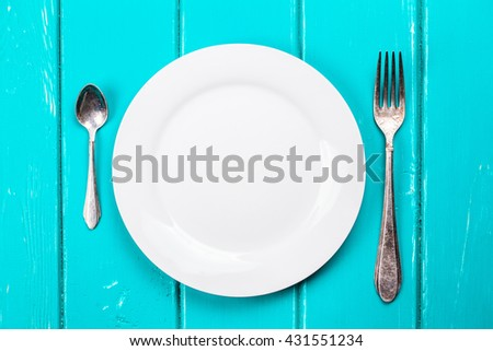 fork and spoon and empty plate on a blue background