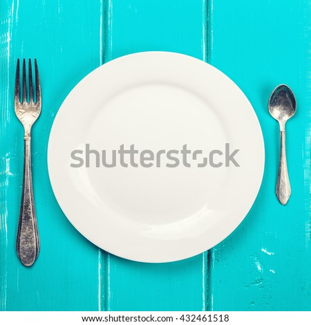 fork and spoon and empty plate on a blue background - stock photo