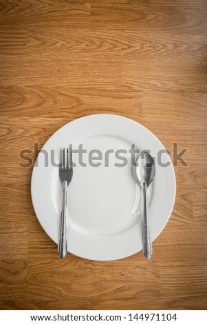 Fork and spoon and Empty white plate on wooden table