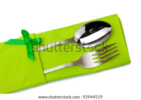 Fork and spoon in a green cloth with a bow isolated on white - stock photo