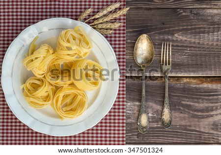 Fork and spoon lying at the old table near the dish with pasta. - stock photo