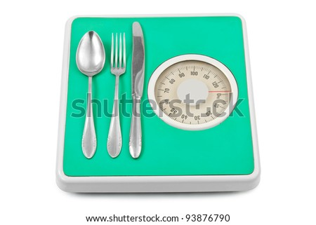 Fork and spoon on weight scale isolated on white background - stock photo