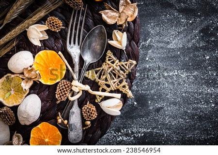 fork and spoon with Christmas decorations on a black textured table - stock photo