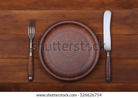 Fork, knife and dinner plate  on a brown wood background - stock photo