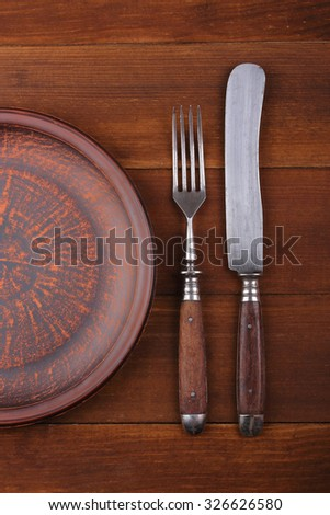 Fork, knife and dinner plate  on a  wood background. Closeup - stock photo