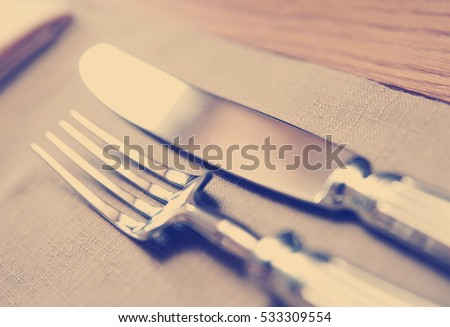 Fork, knife and napkin, very shallow focus, toned image