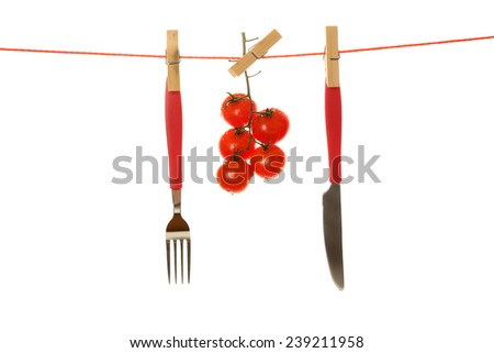 Fork, knife and ripe red tomatoes hanging from clothesline isolated on white background - stock photo