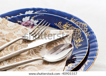 fork knife and spoon on fine blue porcelain - stock photo