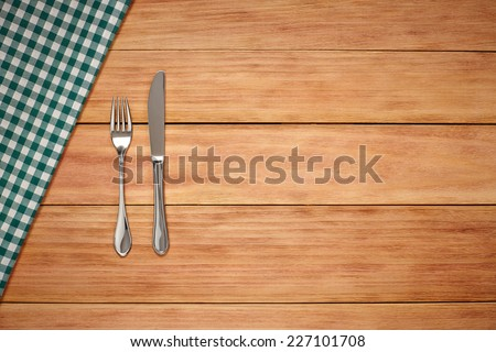 Fork, Knife and Table Cloth on wooden background. Top View with Text Space - stock photo