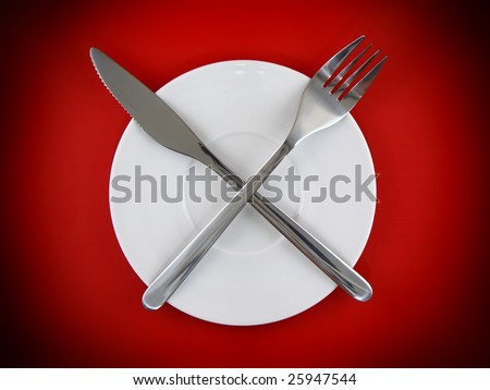 Fork, knife on  red background.Spotlight source on top.