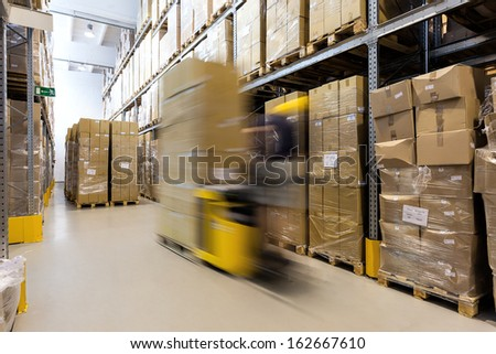 Fork lift operator preparing products for shipment - stock photo