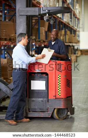 Fork Lift Truck Operator Talking To Manager In Warehouse