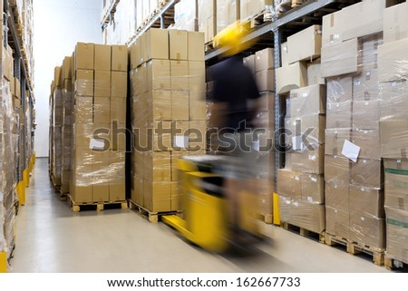 Fork lift with operator working in warehouse