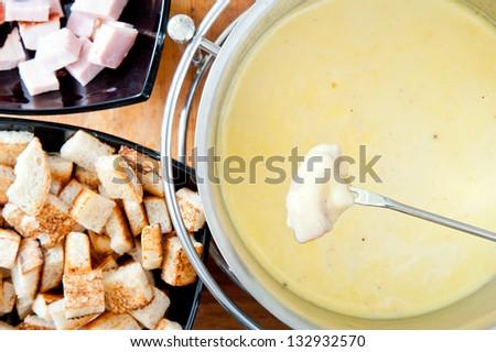 Fork over cheese fondue pot - stock photo