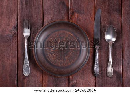 Fork, spoon and knife near the plate. Table setting at a restaurant. Vintage cutlery and a brown earthenware plate. Empty plate. - stock photo