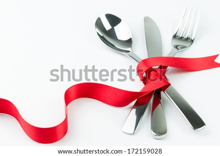 Fork, spoon and knife tied up with red ribbon isolated on white background - stock photo