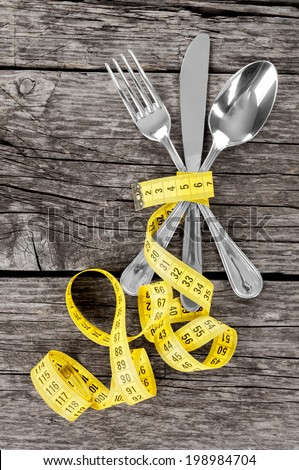 Fork, spoon, knife and measuring tape on a thin wooden background - stock photo