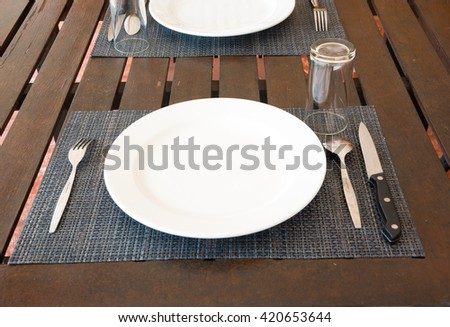 FORK ,WHITE CERAMIC DISH ,SPOON ,WATER GLASS AND KNIFE PREPARED ON THE DARK-BROWN TABLE IN THE RESTAURANT - stock photo