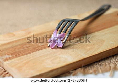 fork with flower wooden plank on table breakfast