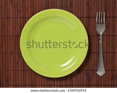 fork with green plate bamboo background. - stock photo