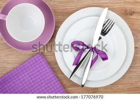 Fork with knife over plates, coffee cup and napkin. On wooden table background with copy space - stock photo