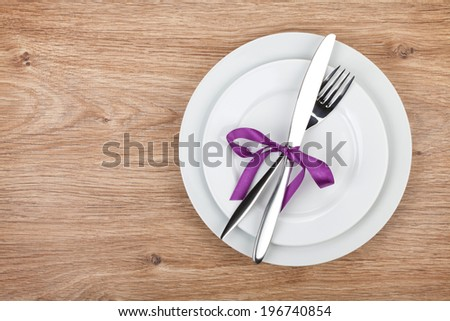 Fork with knife over plates. On wooden table background with copy space