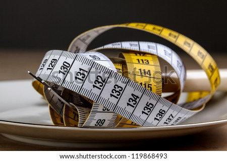 Fork with measuring tape as a symbol of disciplined dieting and weight reduction