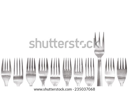 fork with three spikes standing out of the crowd of different shaped normal cutlery - stock photo