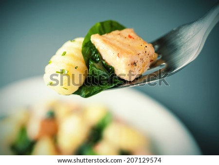 Forkful of grilled salmon, Italian gnocchi and basil seasoned with herbs and spices suspended above the plate with selective focus - stock photo