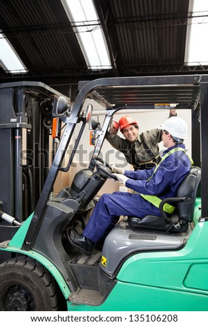 Forklift driver communicating with colleague at warehouse - stock photo
