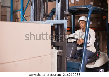 Forklift driver operating machine with boxes on it in a large warehouse - stock photo