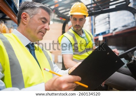 Forklift driver talking with his manager in a large warehouse - stock photo