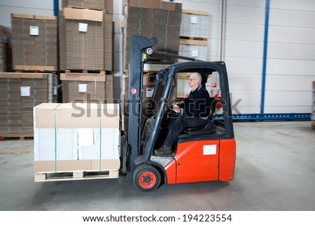 Forklift driving through a nice and clean warehouse. The experienced driver is transporting a pallet full of cardboard boxes. - stock photo