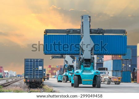 Forklift handling container box loading to freight train in import and export area at port. - stock photo