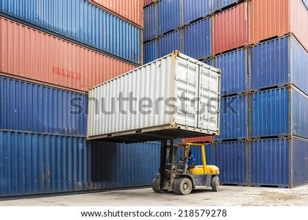 Forklift handling container box loading to truck in import export zone - stock photo