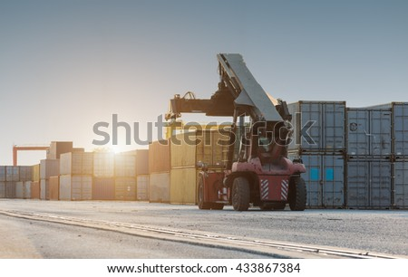 Forklift handling no container box loading at sunset - stock photo