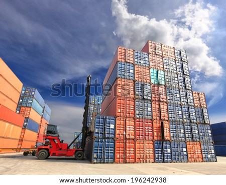 forklift handling the container box at dockyard with blue sky - stock photo