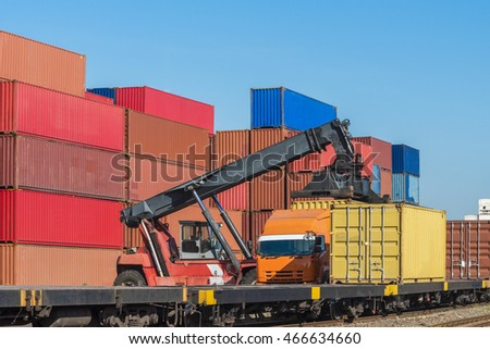 forklift handling the container box from Freight train to truck in logistics area