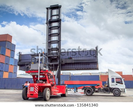 forklift handling the container box load to big truck. - stock photo