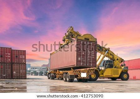 forklift handling the container box packed up transport trucks. - stock photo