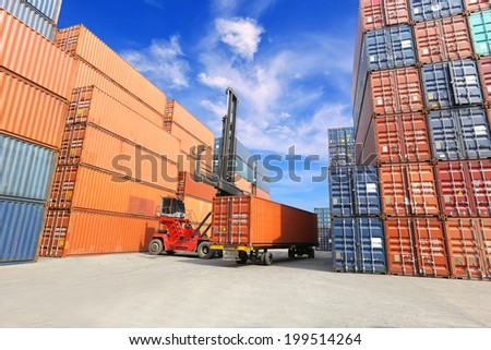 forklift handling the reefer container box at dockyard - stock photo