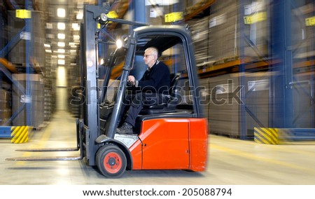 Forklift in a warehouse, driving at speed past the aisles of storage racks - stock photo
