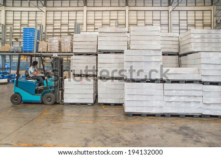 forklift in the large modern warehouse - stock photo