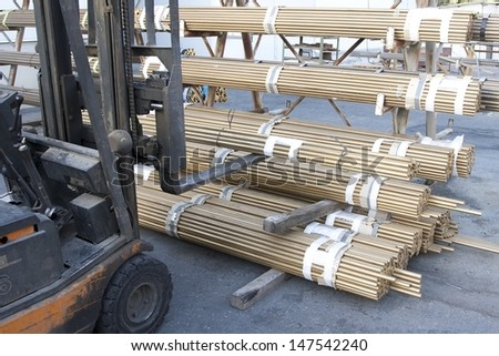 Forklift lifting brass rods - stock photo